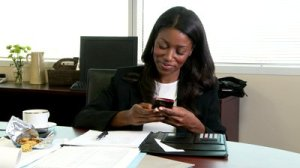 stock-footage-young-business-woman-in-office-texting-on-cell-phone